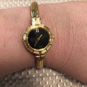 Yves St Laurnet Gold watch with black face.